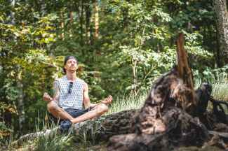 man meditating on a tree log